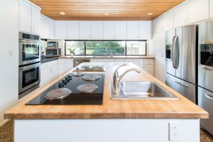 kitchen with wood countertops and brushed metal accents