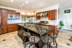 a kitchen with granite counter tops and a dining island