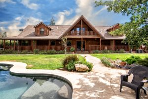a poolside rear view of a wood ranch style home