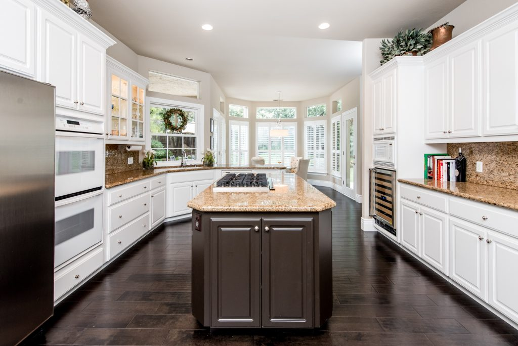 a kitchen island sits center frame atop dark walnut hardwood flooring