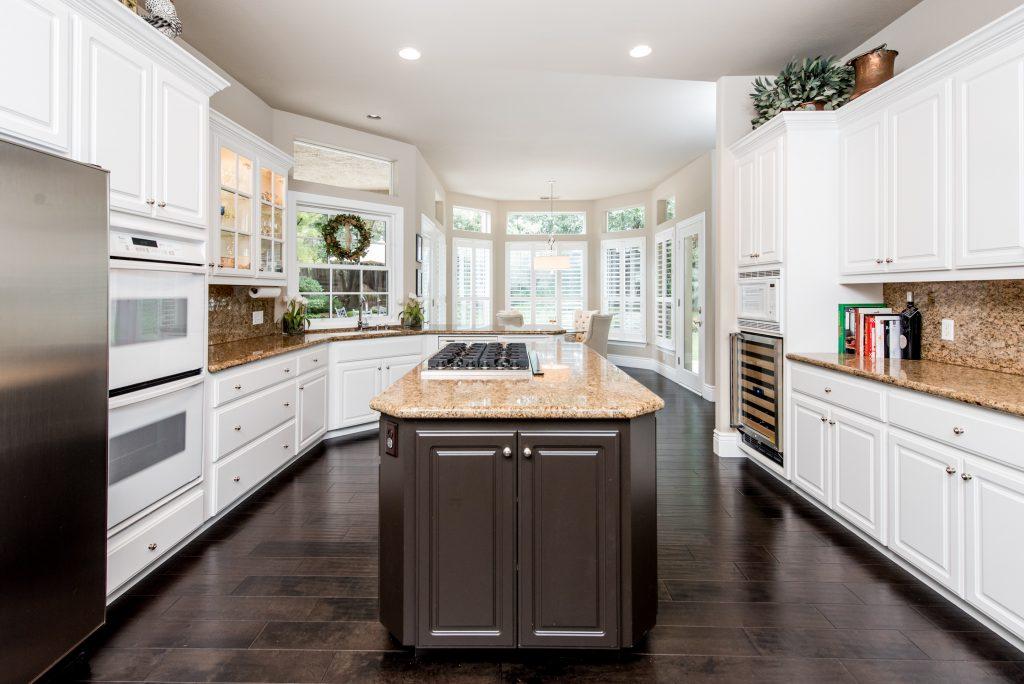 a kitchen island sits center frame atop dark walnut hardwood flooring