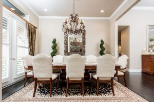 a wooden dining table with white chairs sits atop hard wood floors