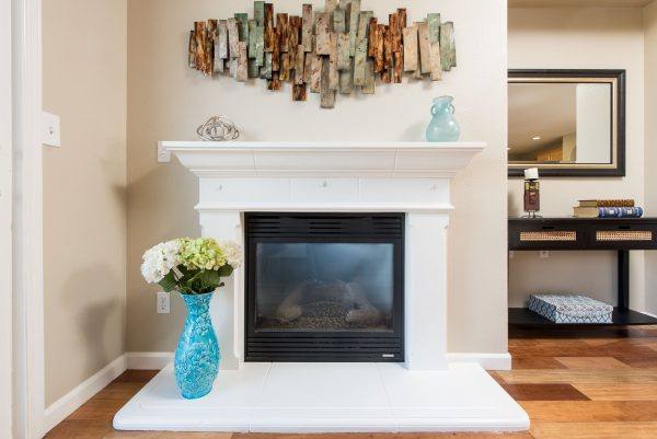 a living room fire place fills the frame, with a wall decoration sitting above the mantle