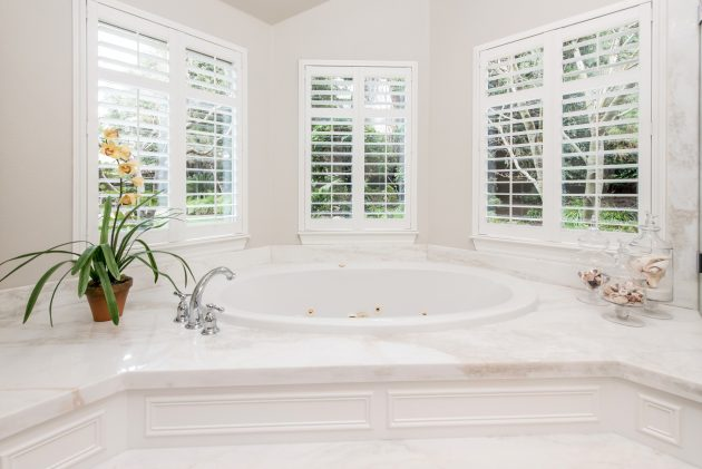 image of a clean, bright bathtub surrounded by a marble platform