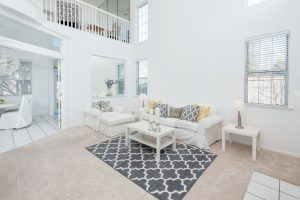 living room with high ceilings and a comfortable white couch
