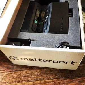 A Matterport 3D camera sits in a box