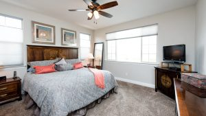 photo of well furnished bedroom, bed sits in focus with pink colored accents