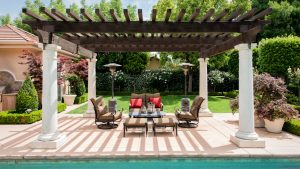 a beautiful backyard patio sits poolside under a luxurious shade structure