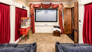 private movie theater room, a large screen fills the center view, popcorn machine on the left