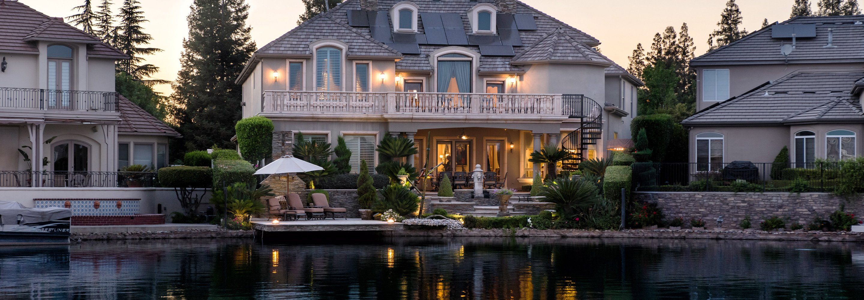 the backyard of a luxury multi story home sits lakeside