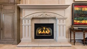 a marble fireplace and mantle housing a comfortable warm fire